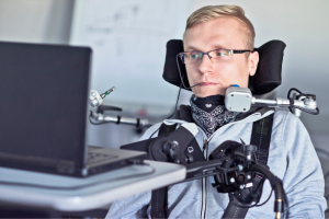 man with paralysis uses laptop computer with the help of technology