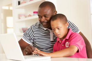 child with intellectual disability using laptop with the help of his father